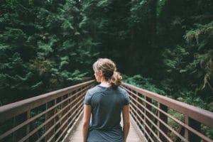 Woman Walking On Bridge In Forrest